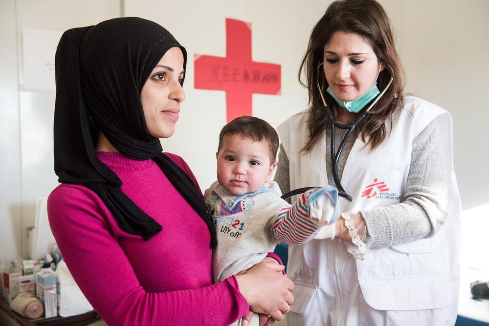 Un'operatrice umanitaria di MSF visita un bambino arrivato con la madre ad Atene dalla Siria