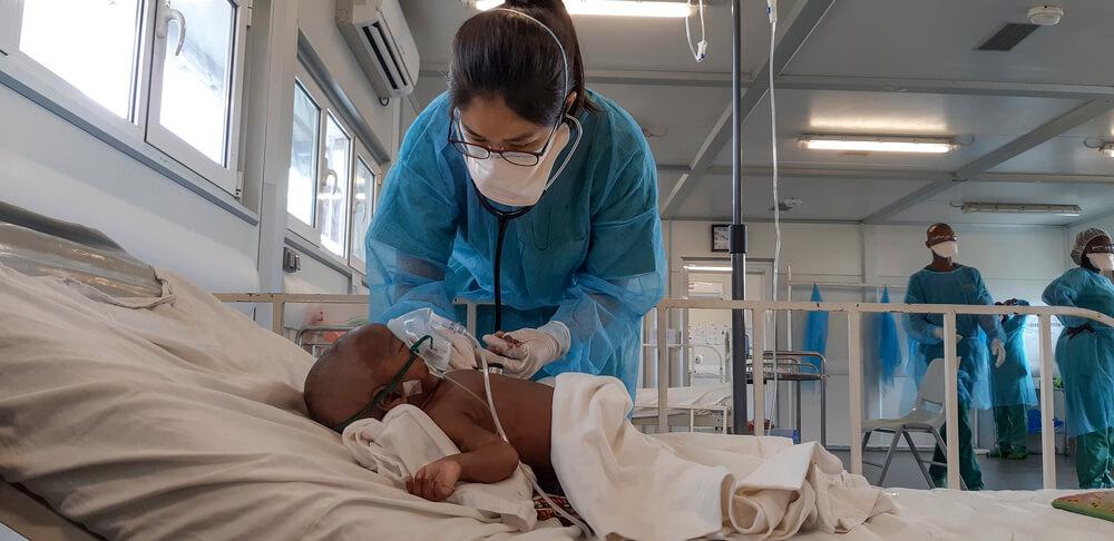 Dottoressa MSF con un piccolo paziente nell'unità di terapia intensiva dell'ospedale di Hangha, distretto di Kenema